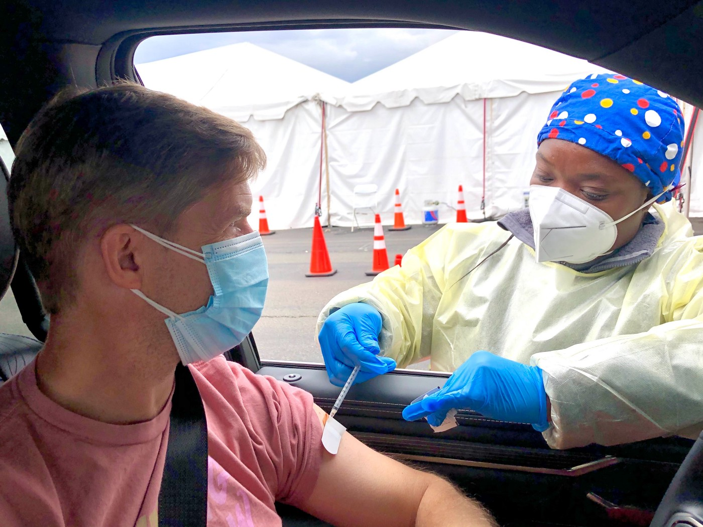 Health-care provider administering Pfizer vaccine to young man in car at drive-up clinic