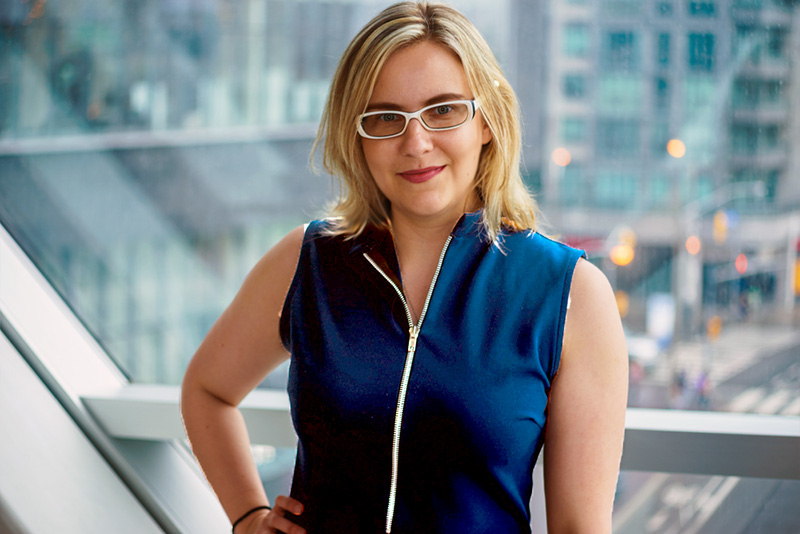 Sarah Kurchak, a white woman with blonde hair and white glasses, smiles into the camera for a portrait. She wears a dark blue shoulderless zip-up top and stands in front of a window that looks out over a city junction.