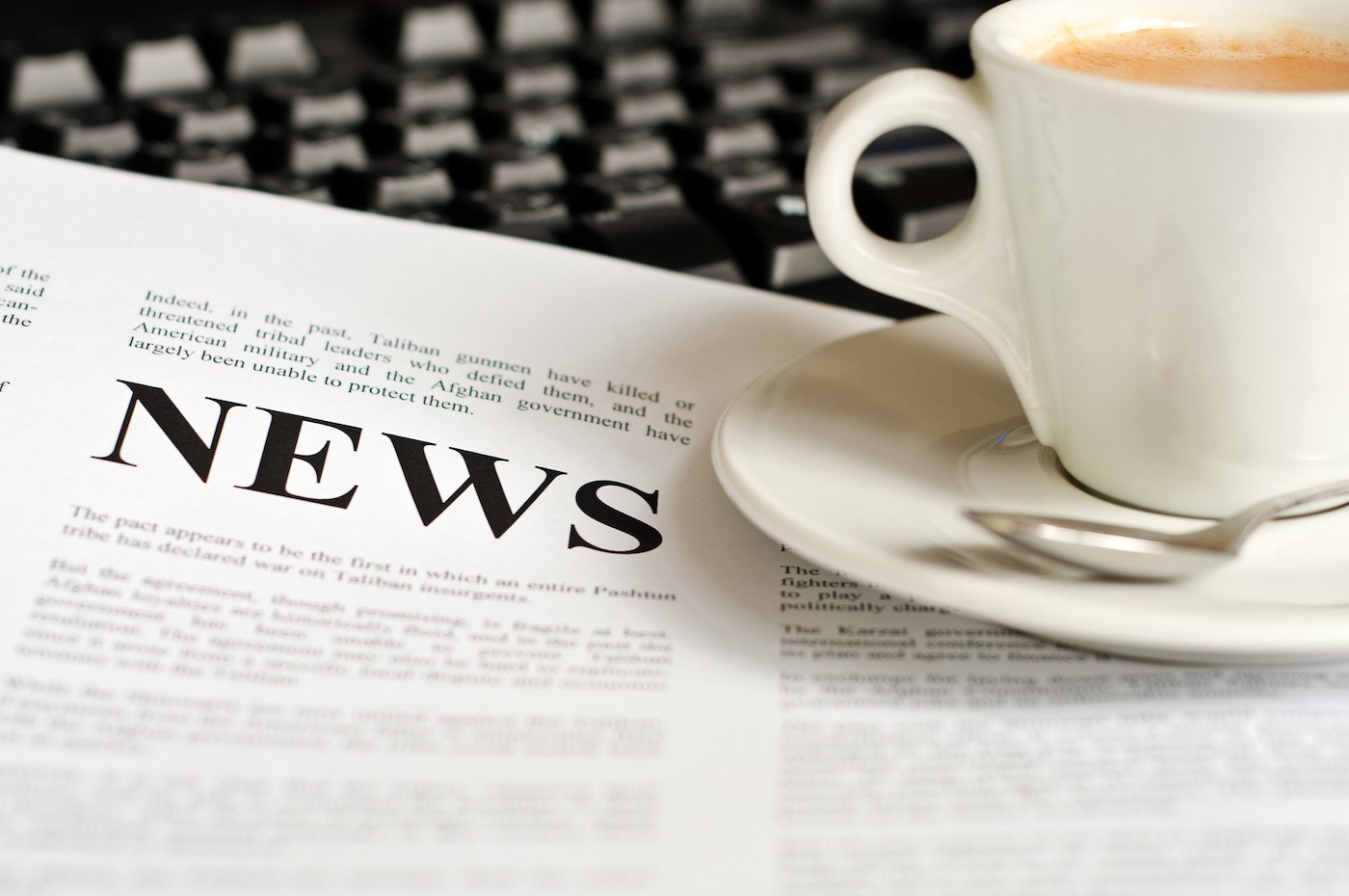 """Newspaper with """"NEWS"""" sitting under white coffee cup"""