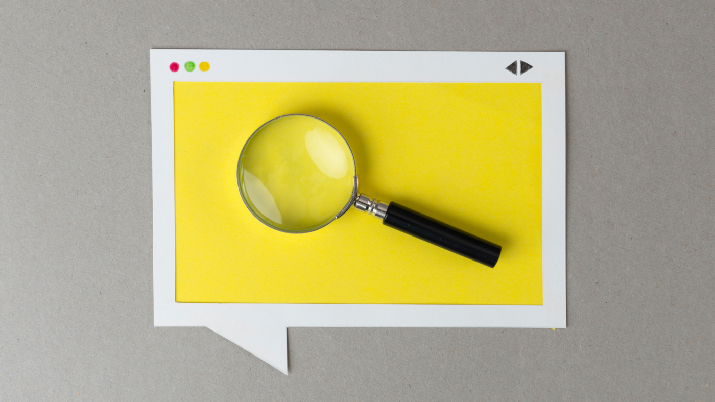 "A yellow arts and crafts cut out of a website screen super imposed inside of ""talking"" dialogue box. There is a magnifying glass on top of the cut out paper image."