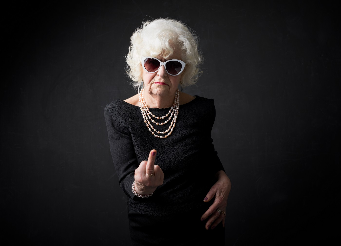 A wealthy elderly woman wearing pearls and sun glasses looks straight into the camera and gives the finger.
