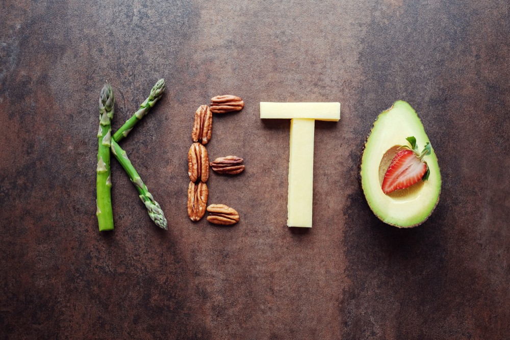 "A photograph of asparagus, pecans, cheesem and avocado arranged to spell ""keto""."