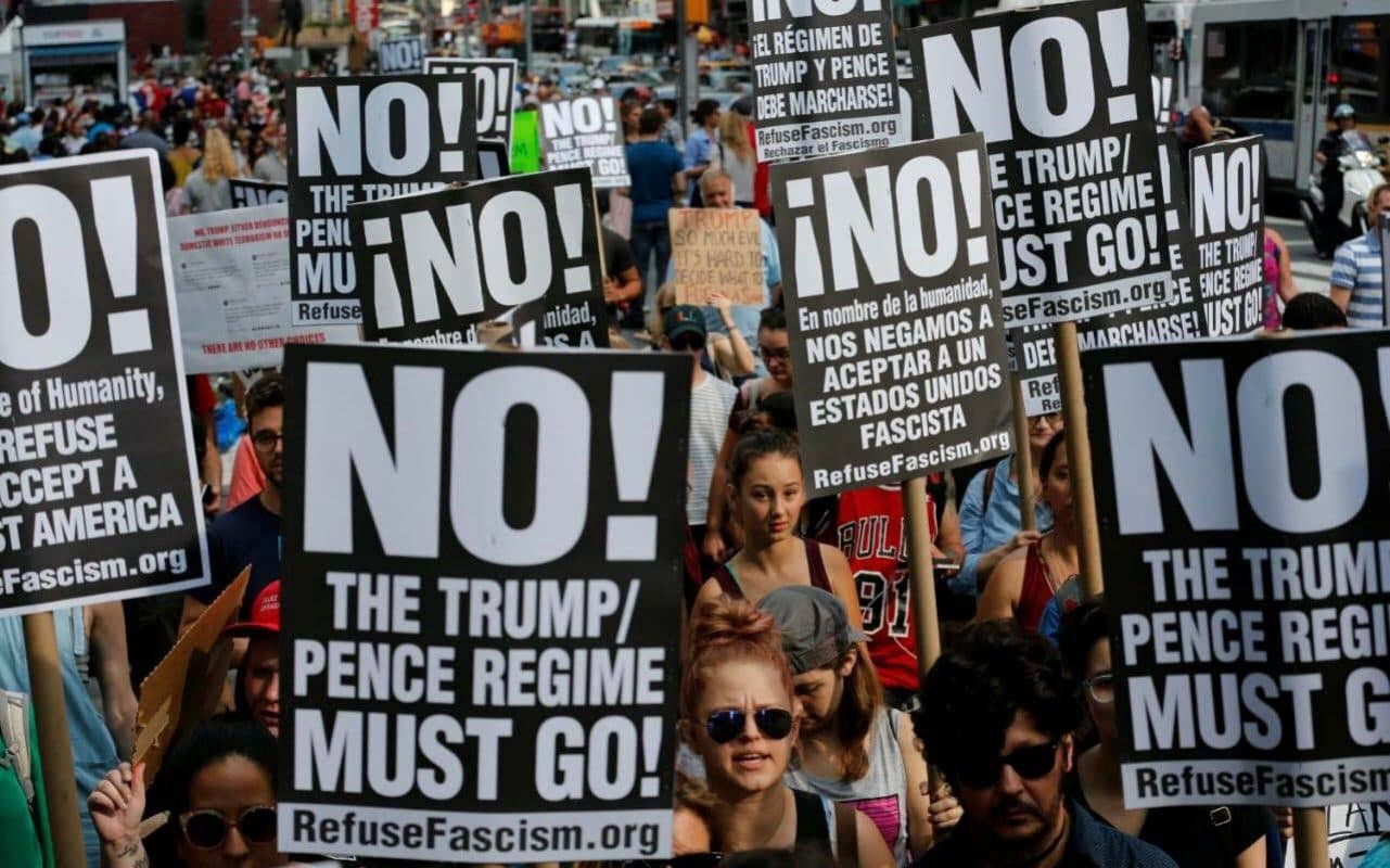"""Refuse Fascism protesters dawn signs with the group's message, """"Trump and Pence must go!"""" (Courtesy of Refuse Fascism)."""