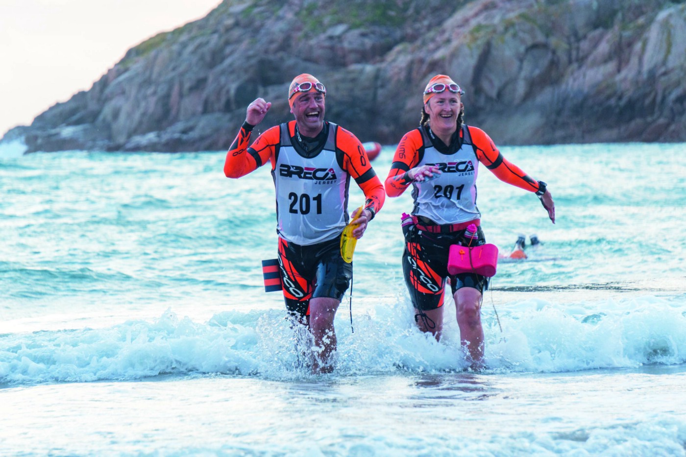A man and woman emerging from the sea during a swimrun event