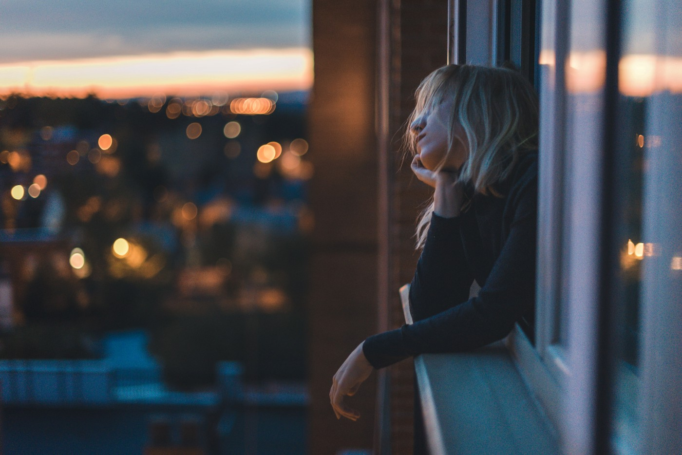 Portrait of a woman leaning on the window at blue hour.