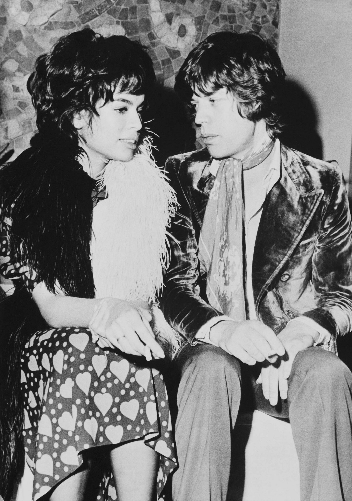 Bianca Jagger (left) in fur and a heart-patterned dress. Mick Jagger (right) wearing a velvet coat and scarf.