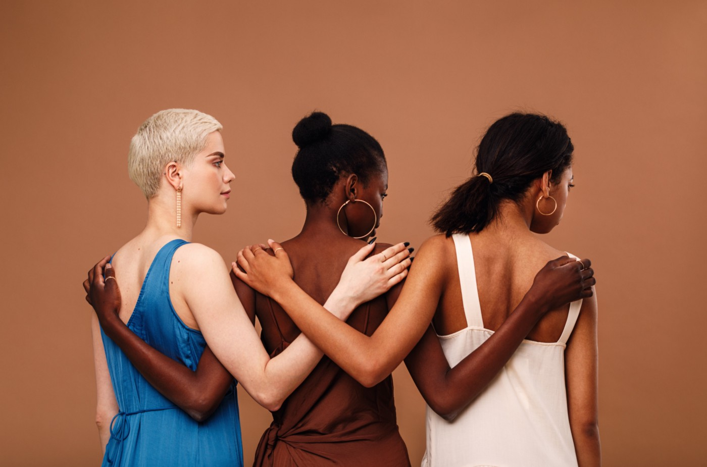 Multi-ethnic women stand with arms on each other's backs, facing away from the camera, against a light chestnut background.