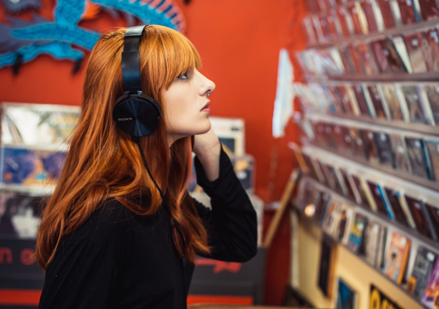 Young woman listening to music and looking at CDs in a music shop