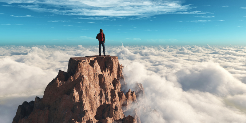 Man standing on top of mountain surrounded by clouds. 5 Types of Content I Write To Scale My Website