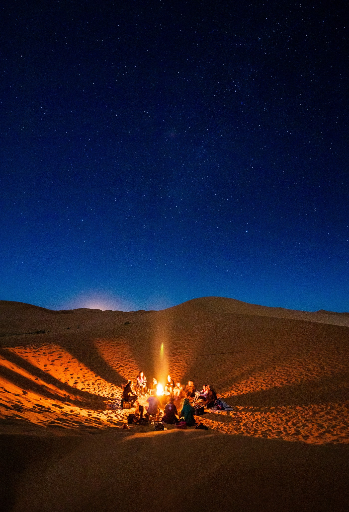 People sitting in a campfire under the night sky.
