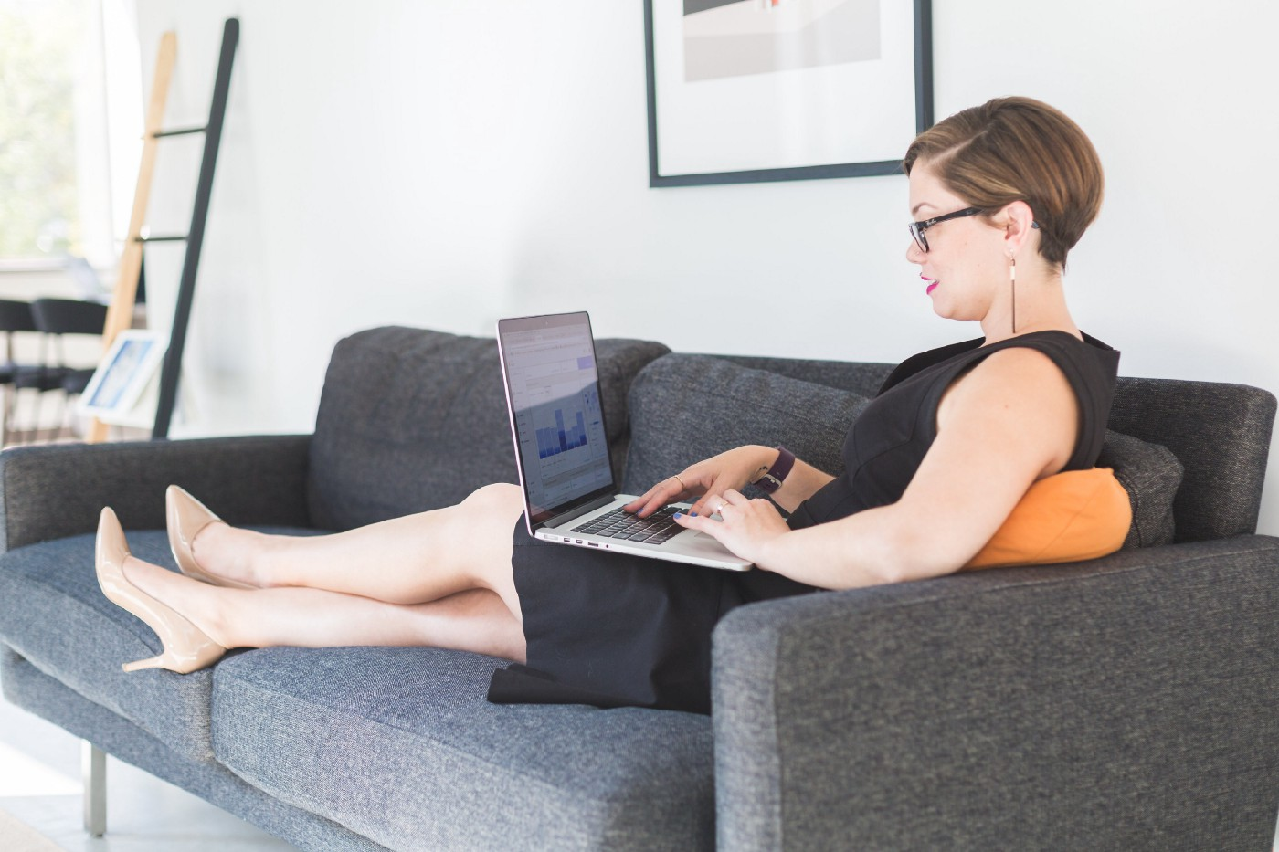 Businesswoman lounging on a couch with her laptop