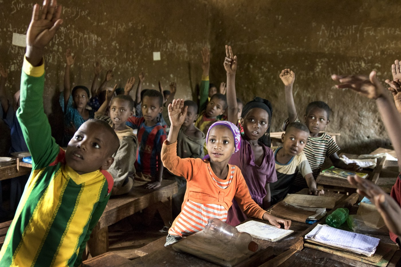 A group of children raise their hands in a classroom.