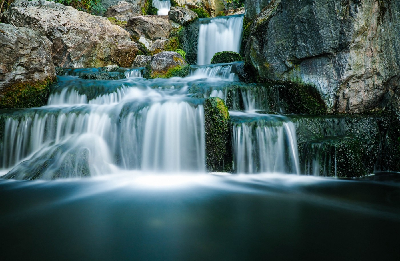 Water flows down a  large, multi-tiered waterfall.