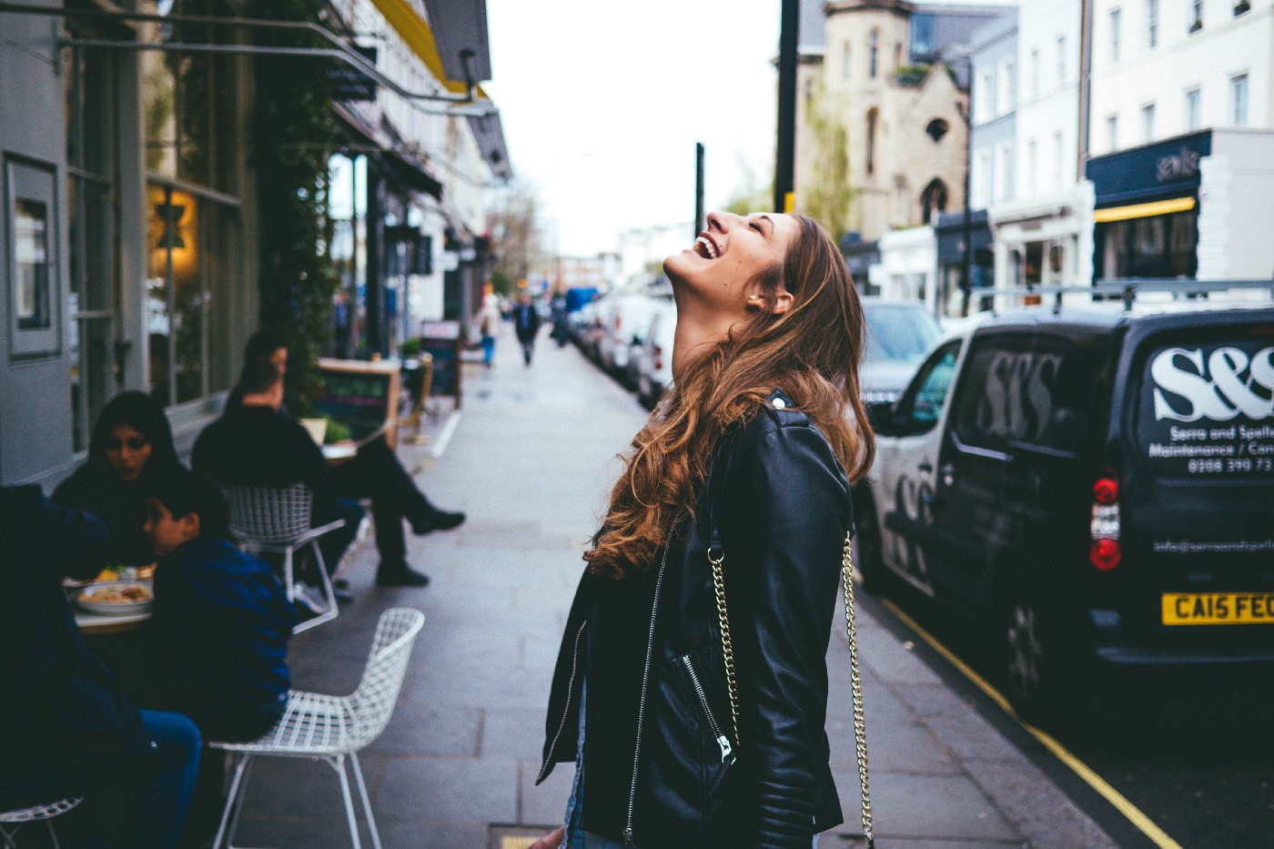 smiling girl with long brown hair wearing black leather jacket standing on sidewalk and looking up to sky