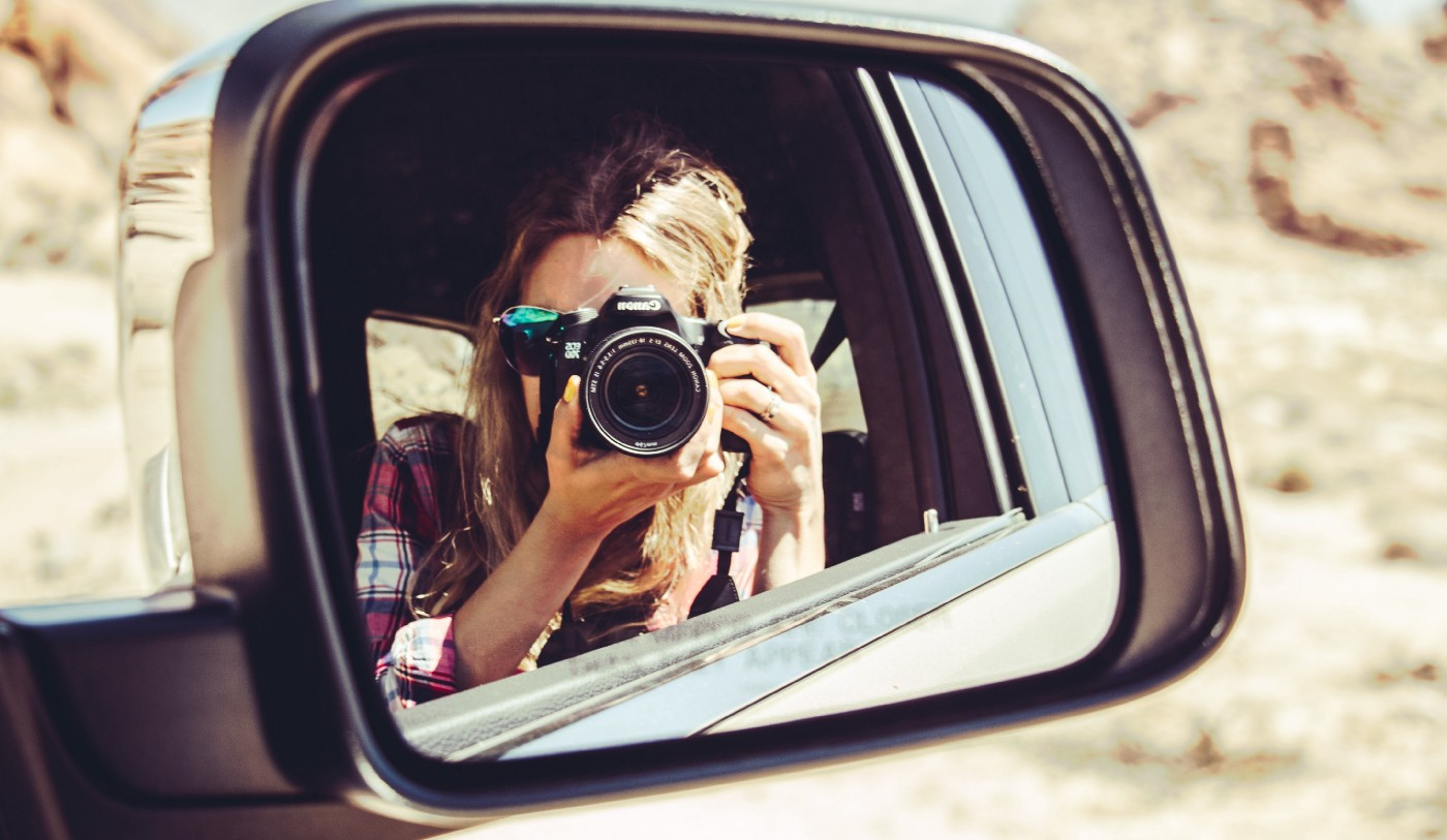 Woman taking photo reflected in car mirror