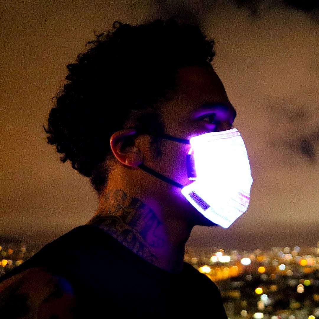 Man wearing LED light-up face mask at night.
