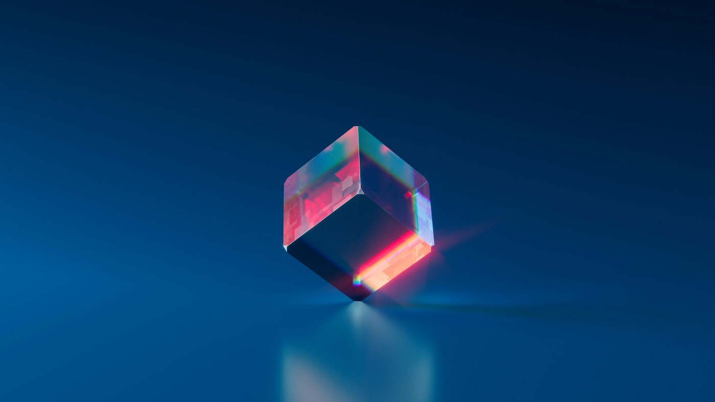 A small, clear cube with colorful light shining through it.