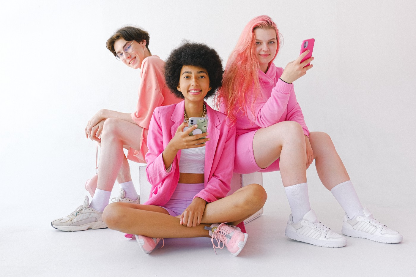 What is Clubhouse and How to Get an Invite—Three teens sitting together with phones in their hands.