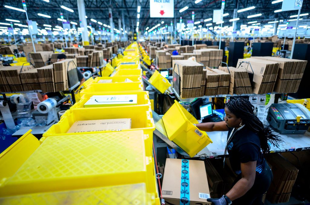 A photo of a woman in an Amazon factory putting packages on the queue line.