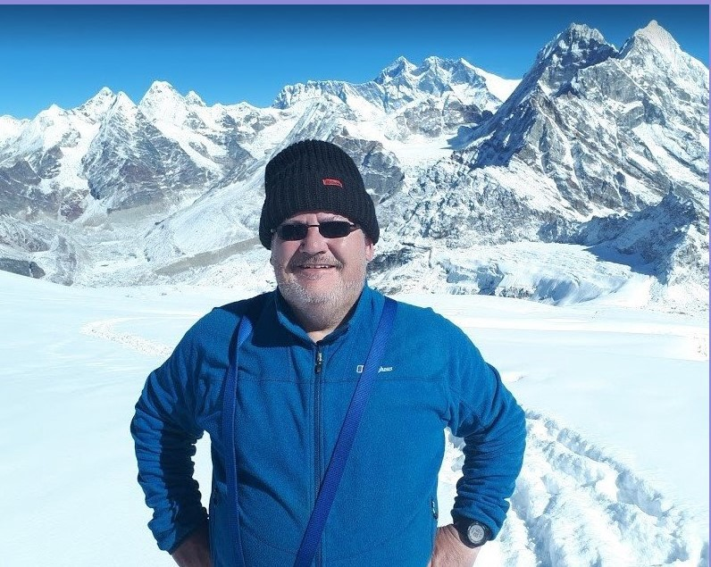 Sean McBride, wearing full winter clothing standing outside High Camp on Mera Peak in the Himalayas. Mount Everest can be seen among the mountains in the background.