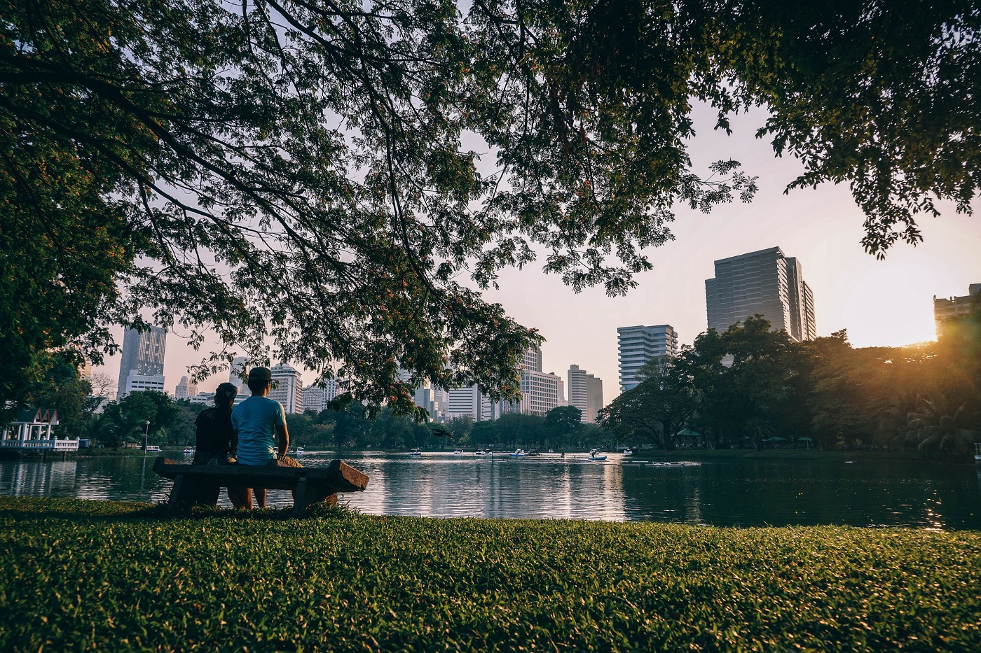 A couple resting on a park bench enjoying the view of skyscrapers in Bangkok.