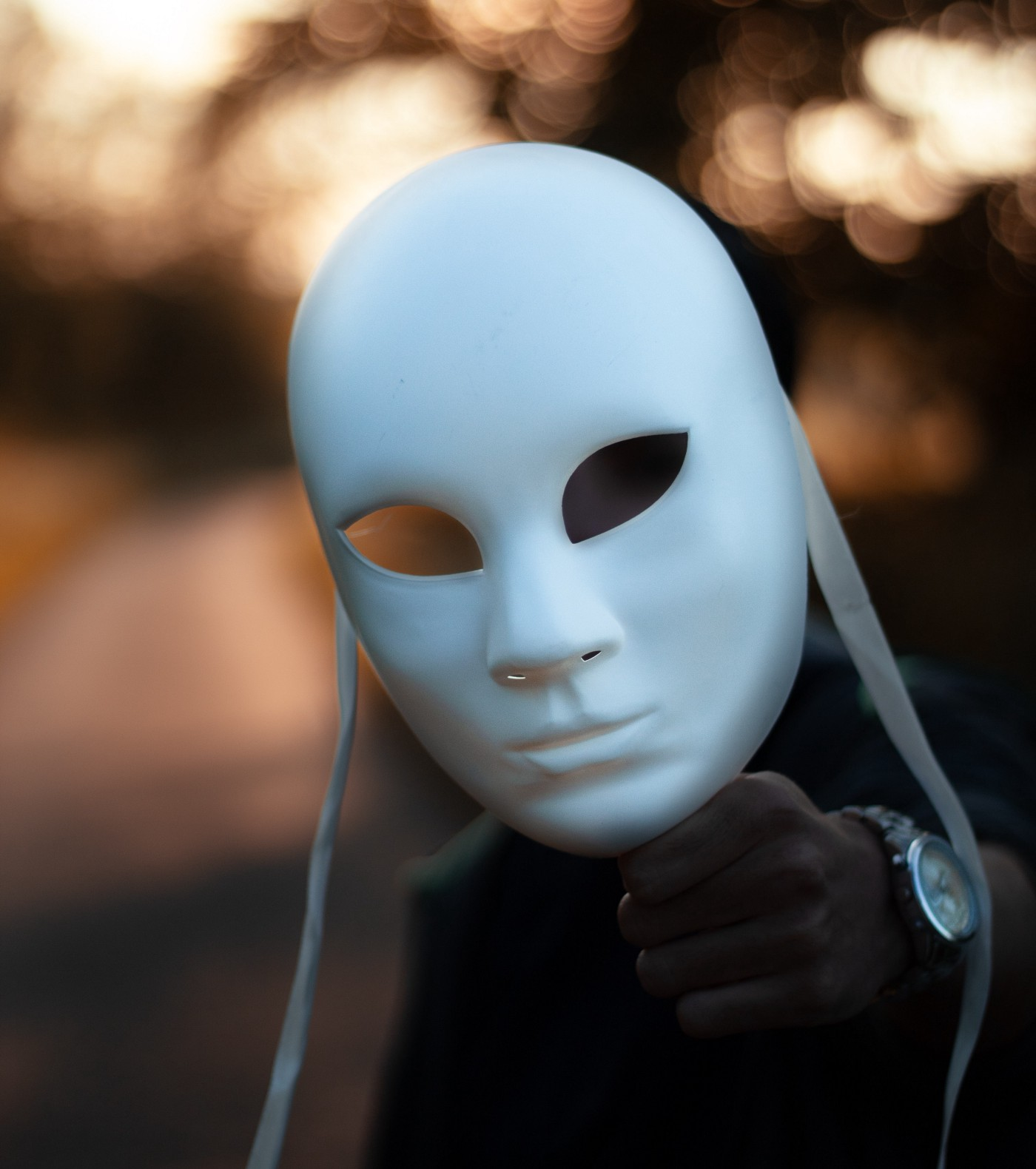 A man holding white mask in front of his facial structure
