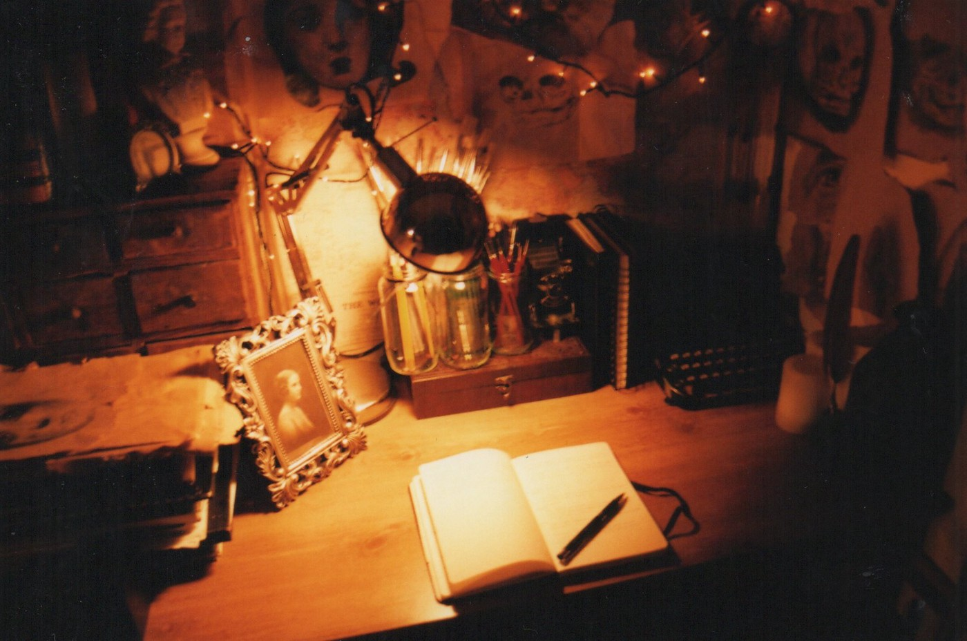 Dimly lit desk with an open notebook with pencil illuminated by a lamp.