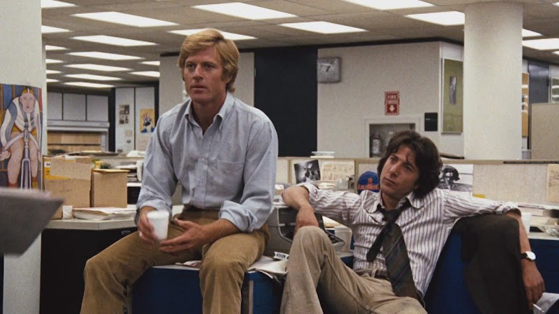 Still from the movie All the President's Men. Robert Redford and Dustin Hoffman casually sit in a newsroom.