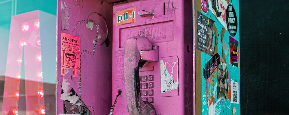 An old payphone that is spray-painted pink with grafitti and stickers all over it.