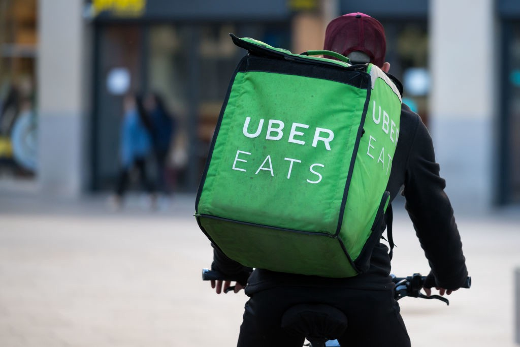 A Uber Eats courier rides a bike through the city center.