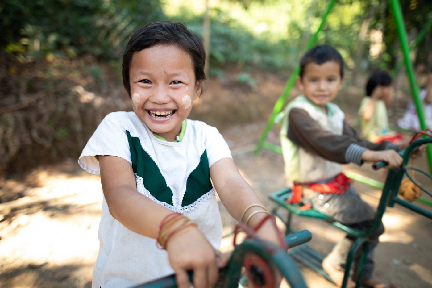 A young Thai girl is wearing a green and white shirt and playing on a playground with several other children.