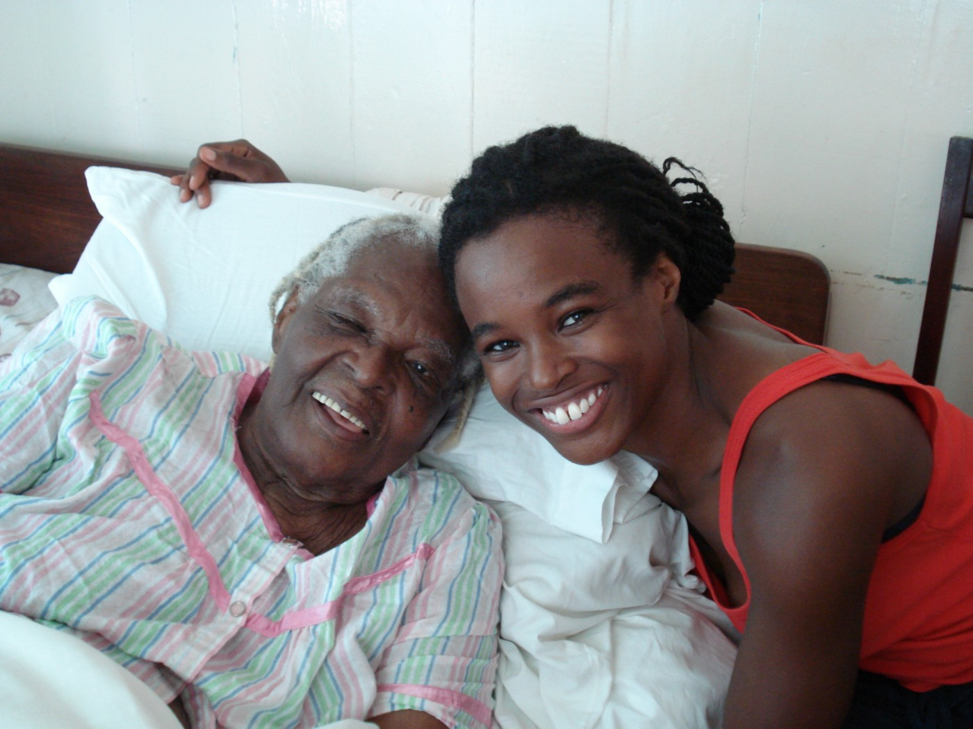 Two Black women smiling head to head, one elderly and bedridden.