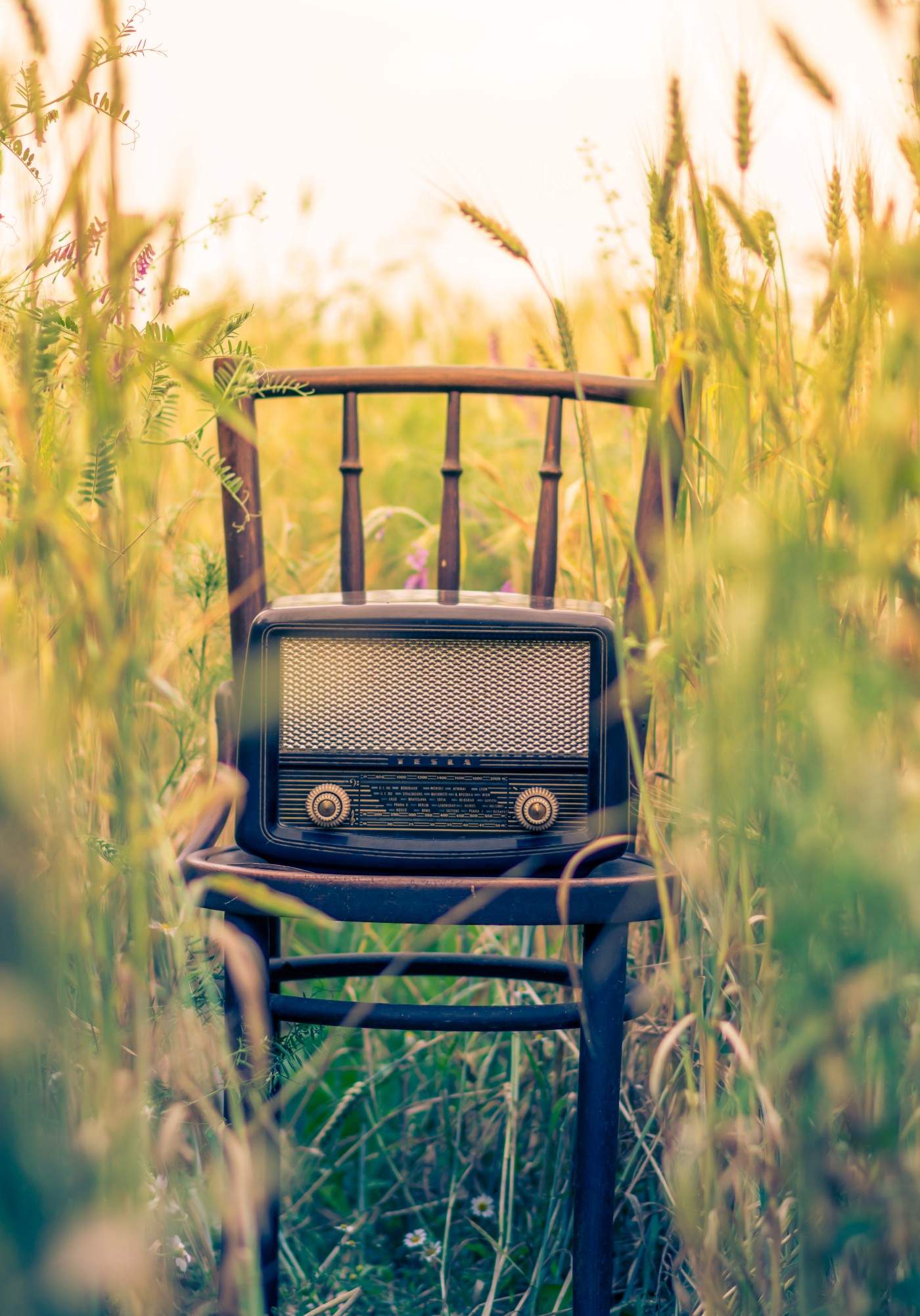the image shows a transistor radio on a chair in a field