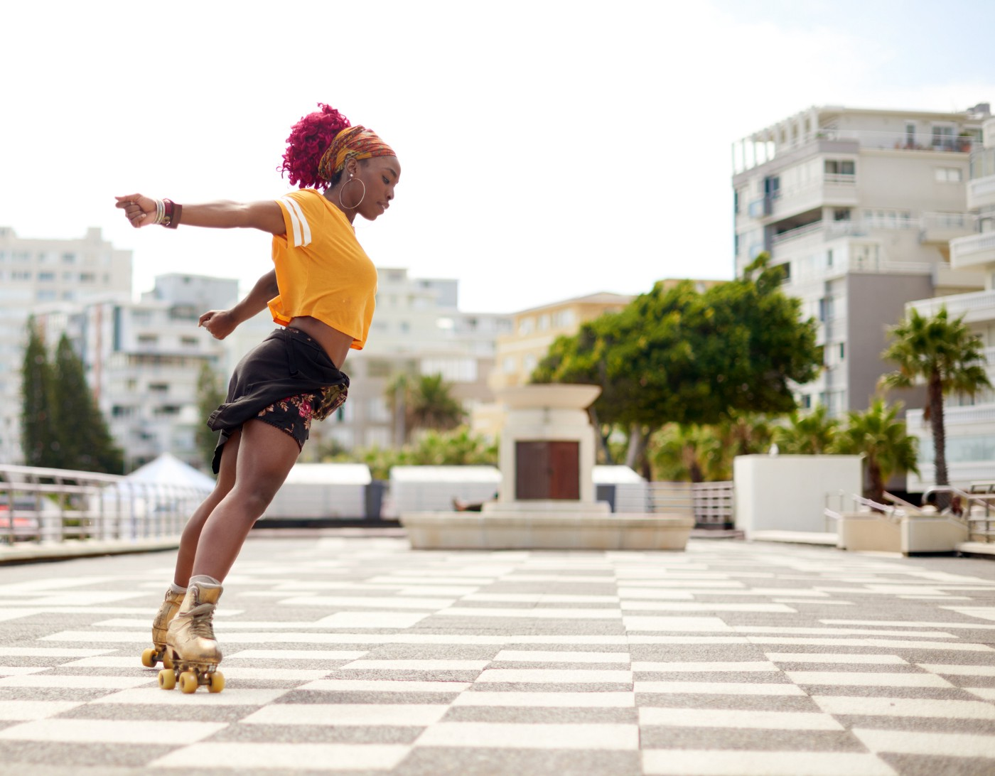 Black woman roller skating outside.