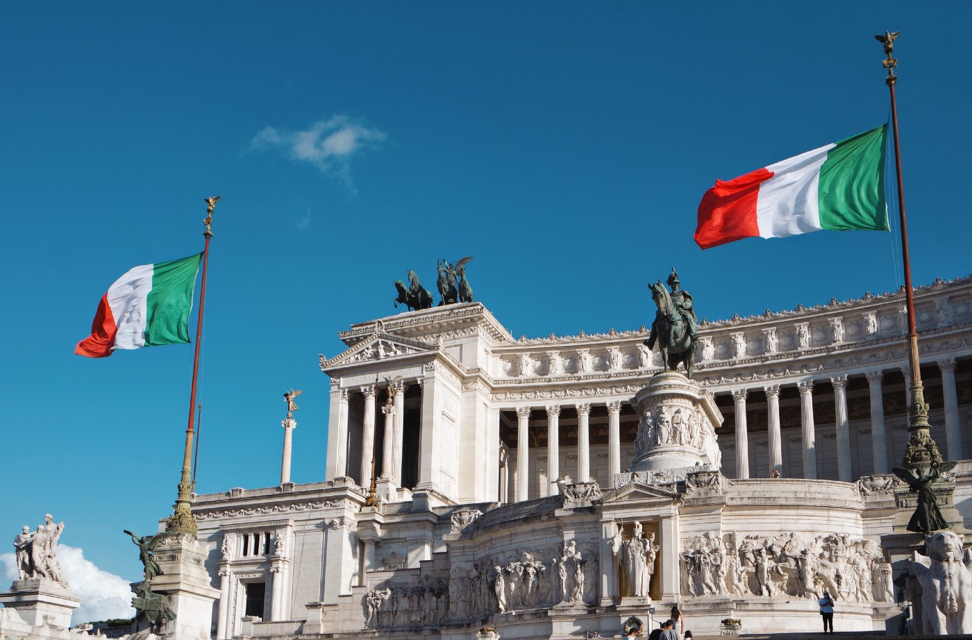 This photo shows the famous Vittorio Emmanuele II Monument in the heart of Rome. There are two Italian flags on each side of the monument and a figure on a horse at the center. There are Roman columns at the front of the building and classical Roman architecture along with embedded bas relief on the building.