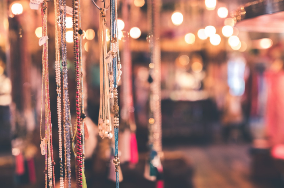 Necklaces are hung up and displayed on a rack inside a store.