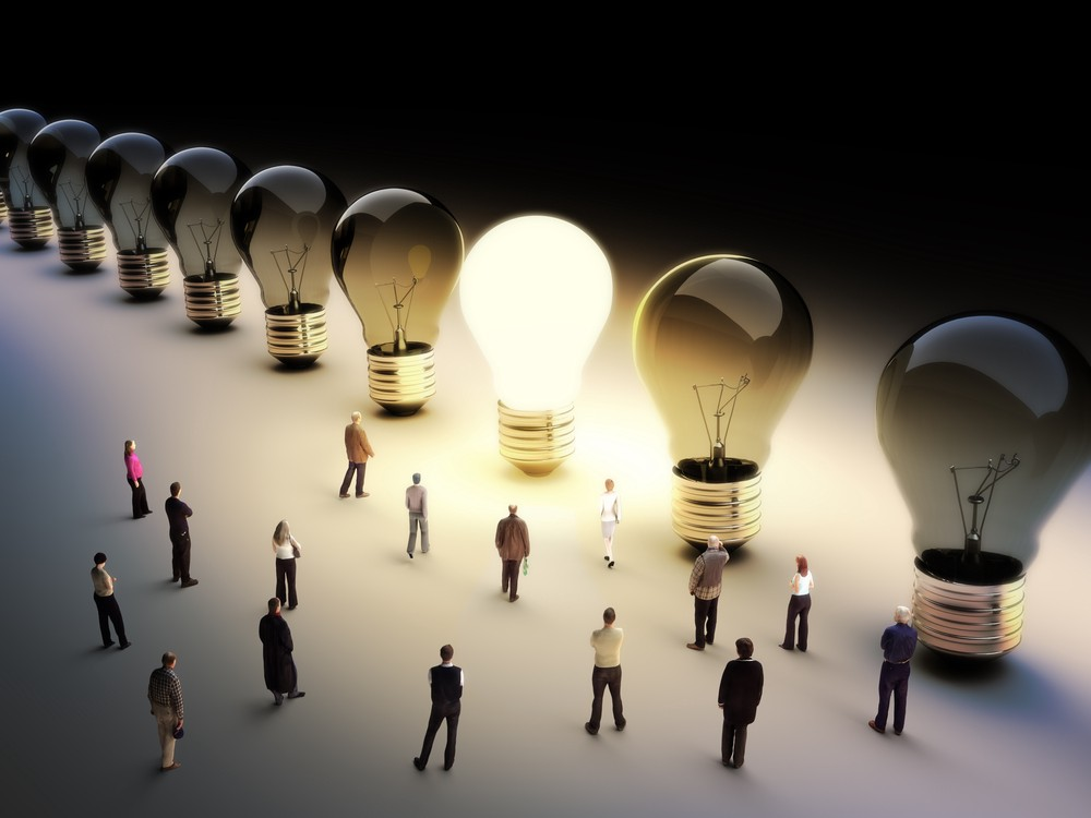A series of people look towards large lightbulbs, all gathering around the only one that's illuminated