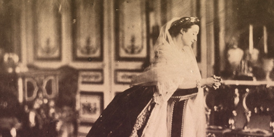 Empress Eugenie in her palace of St. Cloud, wearing a crinoline gown and a white veil.