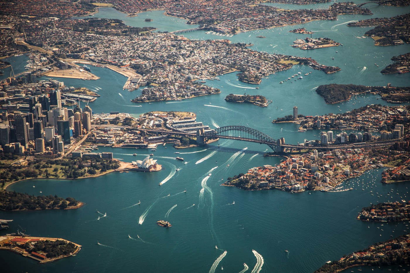An aerial view of the city of Sydney Australia. In the photo you can see Darling Harbor, the Harbor Bridge, and the Sydney Opera House. There are many boats in the harbor leaving white ripples in the water.