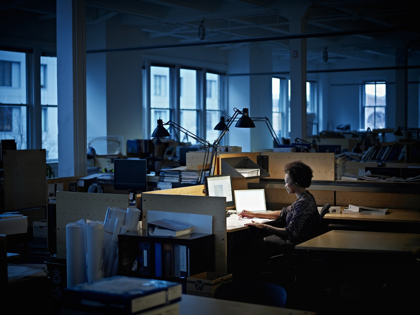 A black woman working alone in a dark office