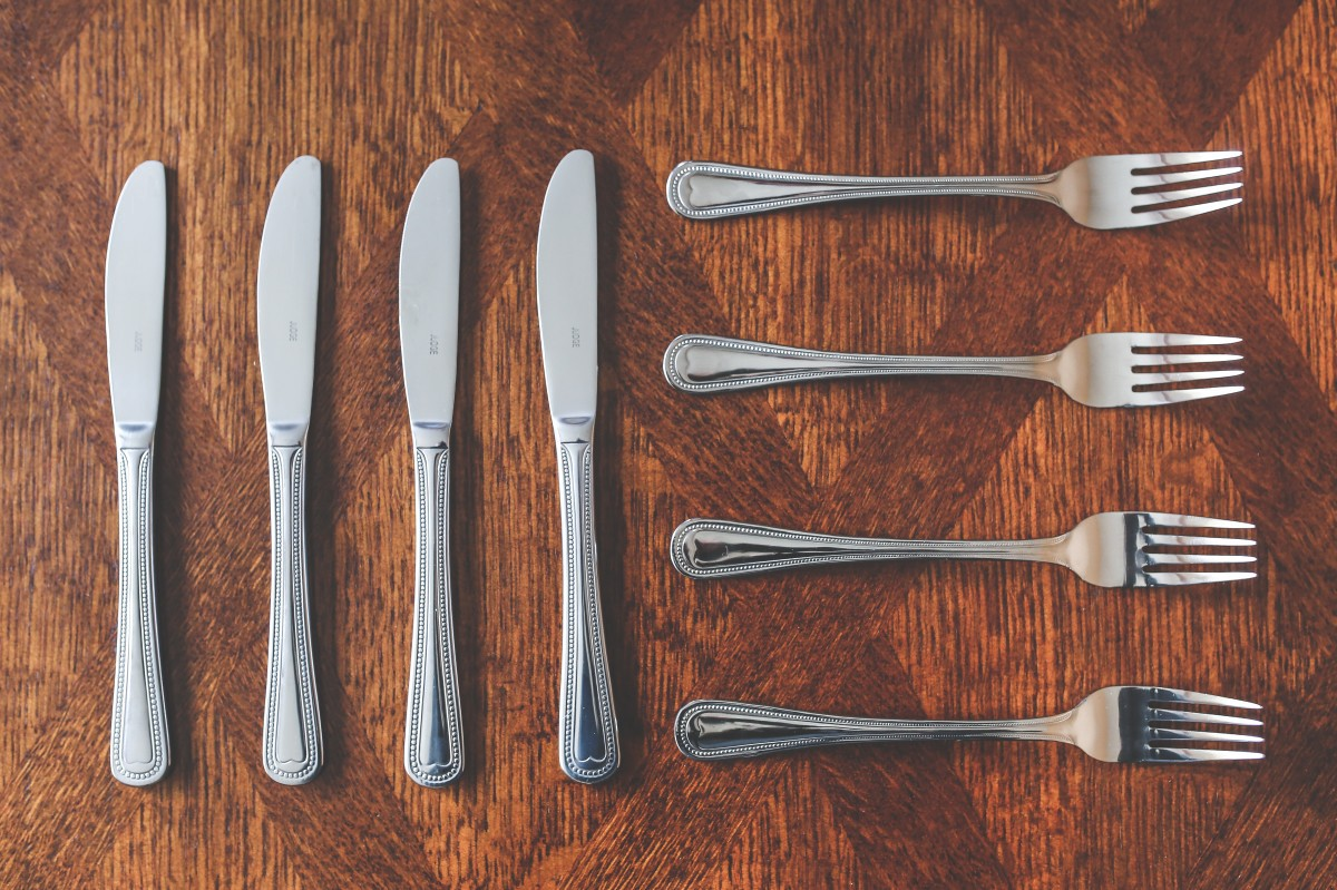 Photo of an arrangement of 4 knives vertically oriented on the left and 4 forks horizontally oriented on the right