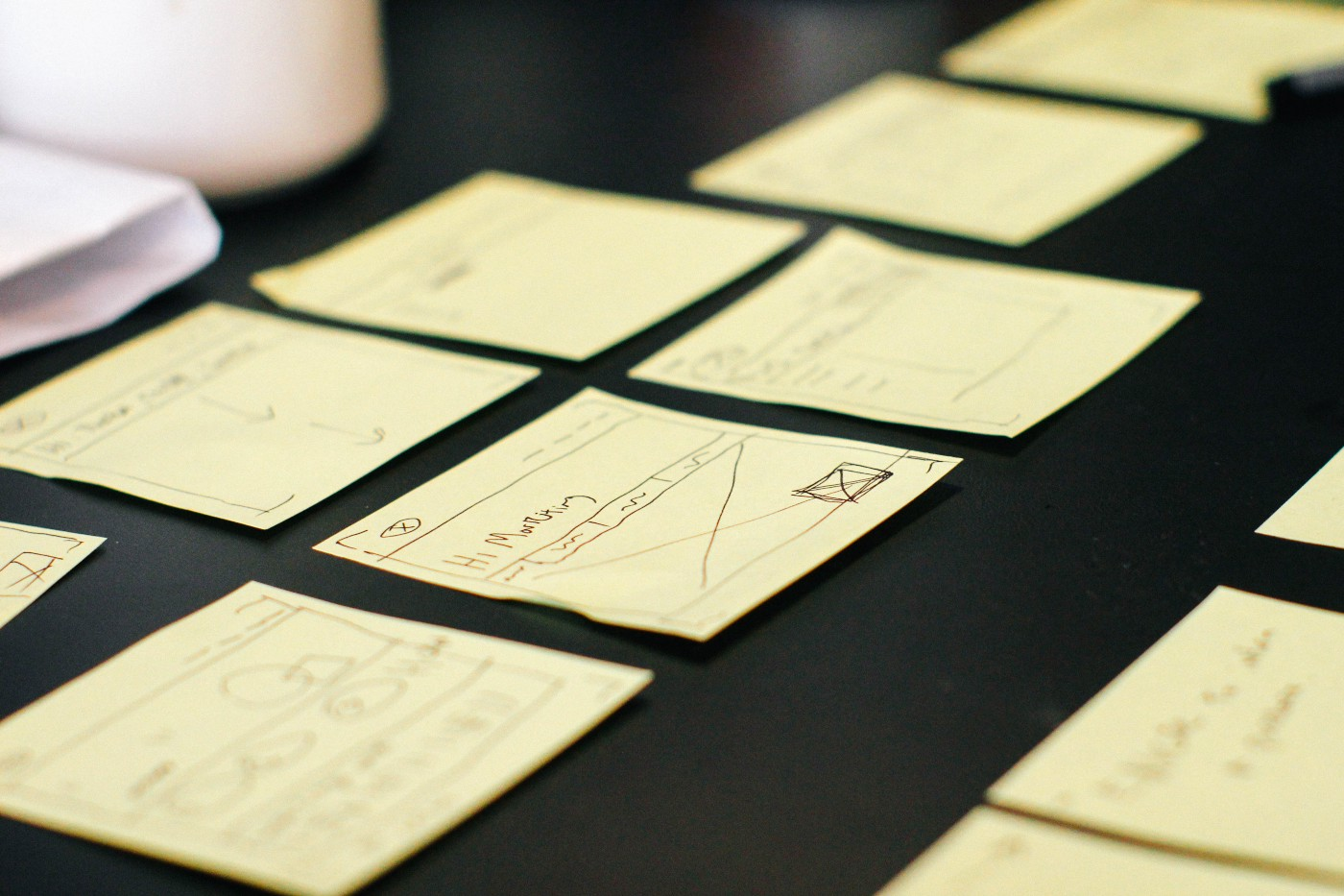Yellow sticky notes on black desk—a common sight at startups for brainstorming ideas, organizing thoughts and tracking task