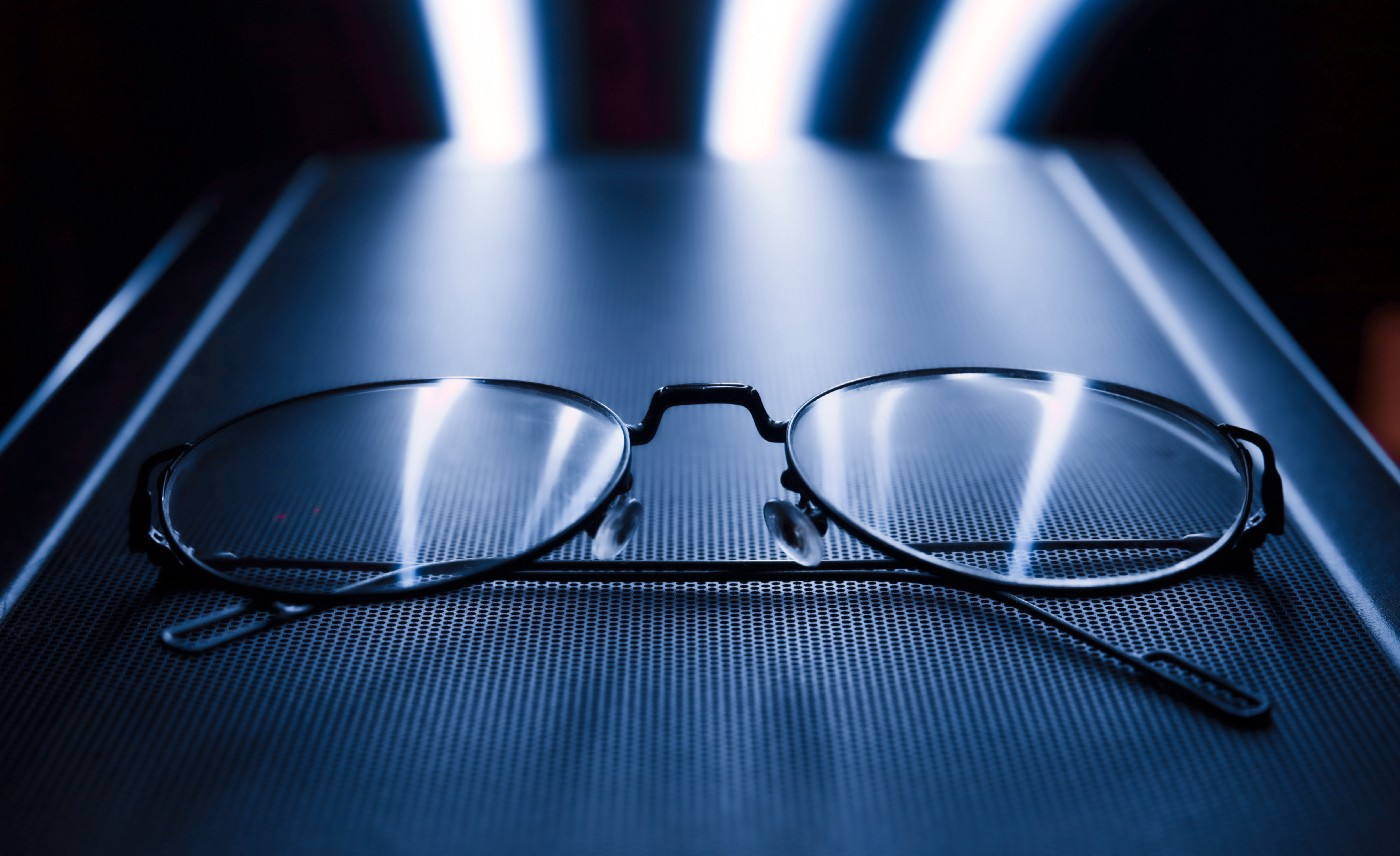 Close up of thin black eyeglasses frame on a dark blue surface with LED lights in the back.