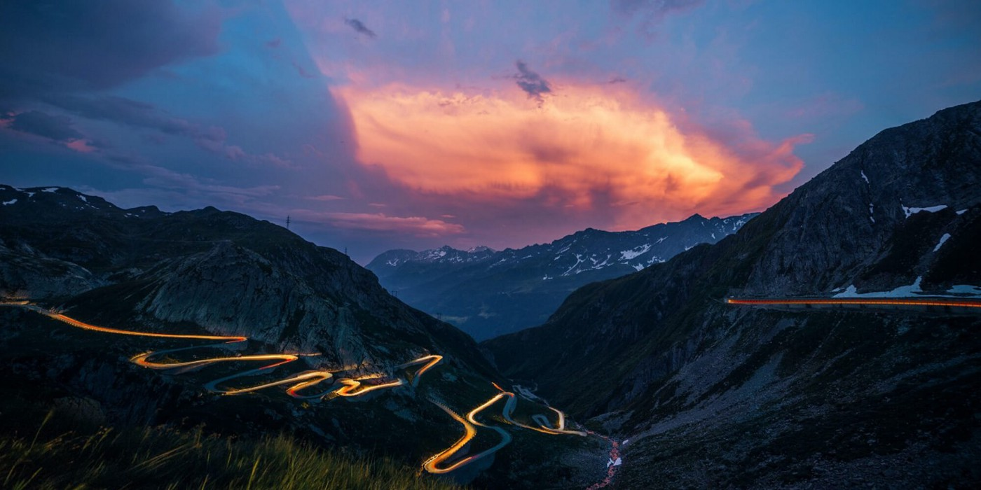 Sunset behind a mountain with a lit up winding road heading down the mountain