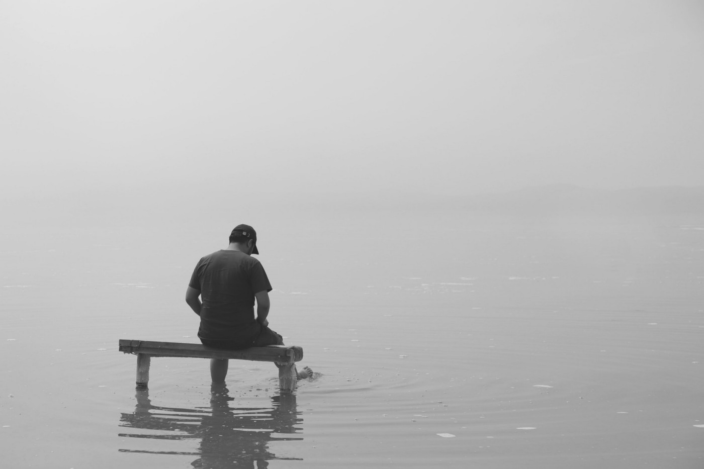 A person sitting on a bench that is underwater.