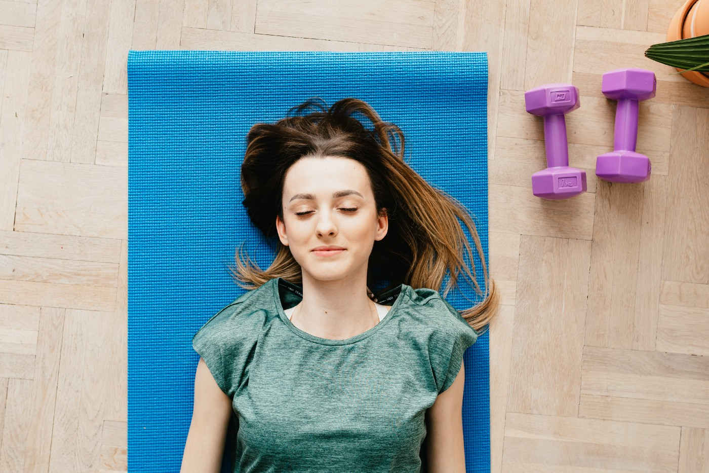 Girl lying on a yoga mat with closed eyes.