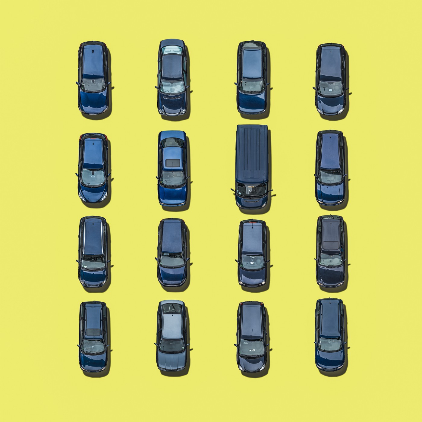 An aerial view of 16 blue cars on yellow background.