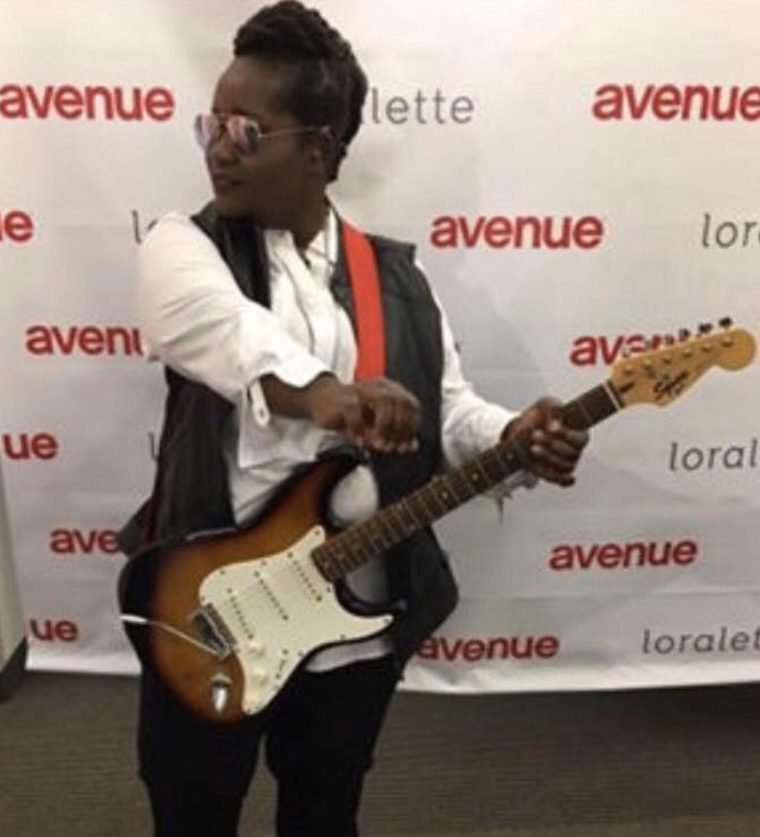 CaspHer (Casandra) standing in front of an Avenue plus-size modeling billboard posing with her own electric guitar.