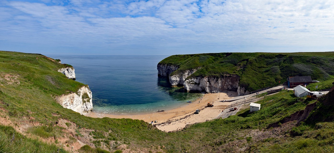 View of North Landing, Flamborough, Yorkshire, UK—chalk headlands either side with sandy bay on a sunny day.