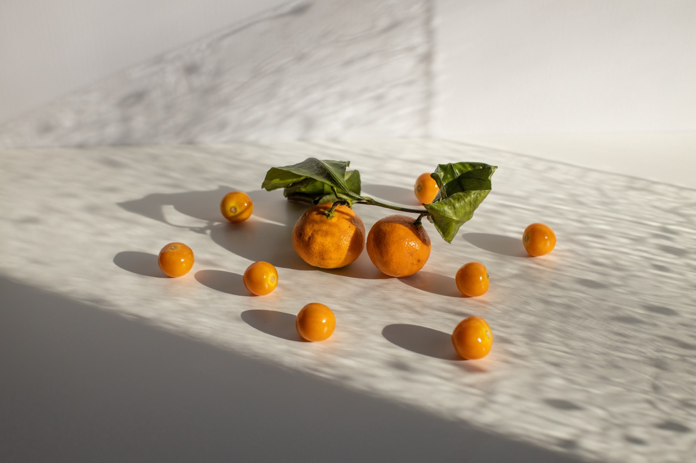 tangerines and groundcherries scattered on white surface in daylight